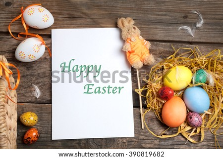 Easter composition with eggs and a postcard on the table - stock photo