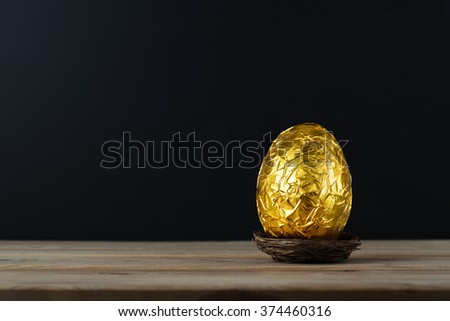 Easter concept.  A chocolate egg, wrapped in crinkled metallic gold foil.  Presented in a small nest on a wood plank table with black chalkboard background providing copy space. - stock photo