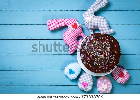 easter concept with cake, eggs and rabbit on wooden table
