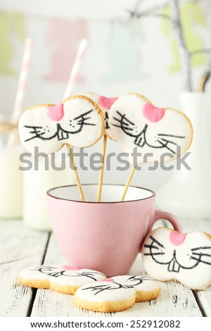 Easter cookies in cup on white wooden background - stock photo