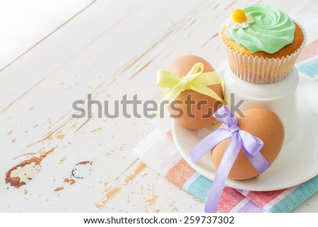 Easter cupcake and eggs decorated with yellow and violet ribbons, white wood background - stock photo