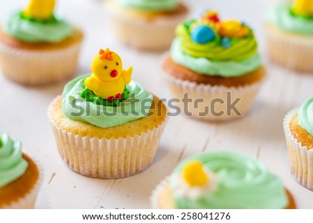Easter cupcakes decorated with chick and eggs sugar figures, white wood background - stock photo