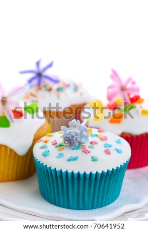 Easter cupcakes with spring flowers on white isolated background - stock photo