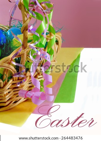 Easter d�©cor is closeup of an Easter basket filled with grass and plastic eggs. The basket is adorned with pink and green ribbons. There are layers of yellow, pink and green paper. Background is pink - stock photo