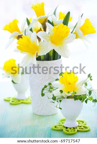 Easter decoration: narcissus in vase and eggcups - stock photo