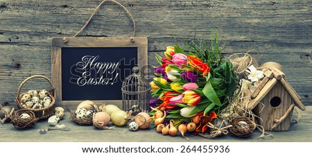 Easter decoration with eggs and tulip flowers. Vintage background with sample text Happy Easter! Retro style toned picture. - stock photo