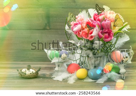 Easter decoration with pink tulips, butterflies and colored eggs. Retro style toned picture with light leaks. - stock photo