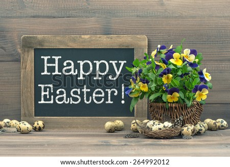 Easter decoration with quail eggs, pansy flowers and vintage blackboard with sample text Happy Easter! Retro style toned picture - stock photo