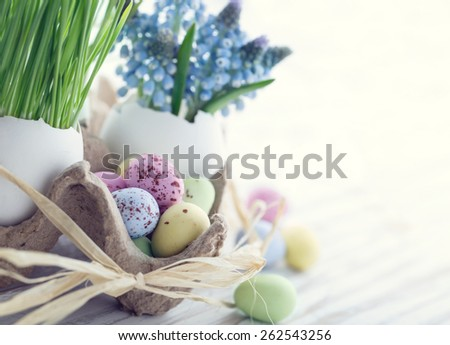Easter decoration with small chocolate eggs, green grass and blue muscari flowers with hazy vintage editing - stock photo