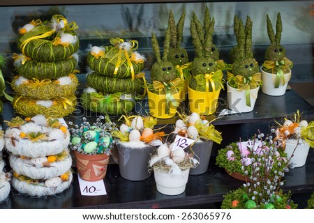 Easter decorative wreath nest with colored eggs, bows, ribbons, grass and feathers, funny rabbits made from grass hay, pussy-willow bouquets in pots, colorful decorations with moss - stock photo