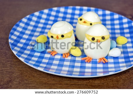 Easter deviled eggs with candy eggs on blue and white checkered plate - stock photo