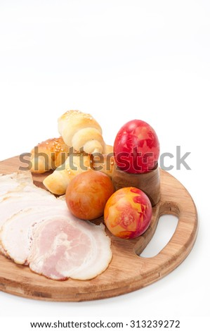 Easter egg, bacon and croissants on a wooden board. - stock photo