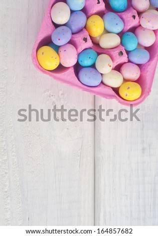 Easter Egg Candies in a Pink Egg Carton on Rustic White Board Background viewed from top or above with space or room for text, copy, or words.  Vertical - stock photo