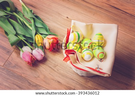 Easter egg decorations in a basket with beautiful tulips - stock photo