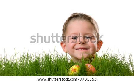 Easter egg hunt. Cute boy searching for easter eggs hidden in fresh green grass. Isolated on white background