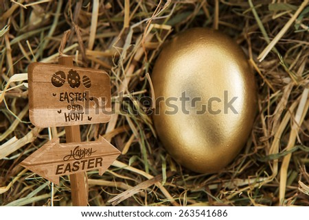 Easter egg hunt sign against golden egg in the straw - stock photo