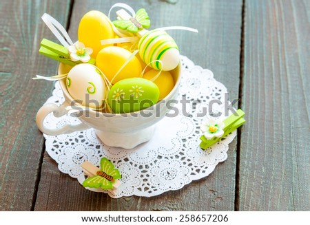 Easter egg in a tea cup, green and yellow colored - stock photo