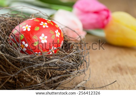 Easter egg in the nest with flowers on wooden table - stock photo