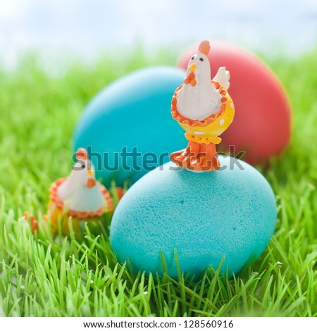Easter egg with chicken toy in green grass, selective focus
