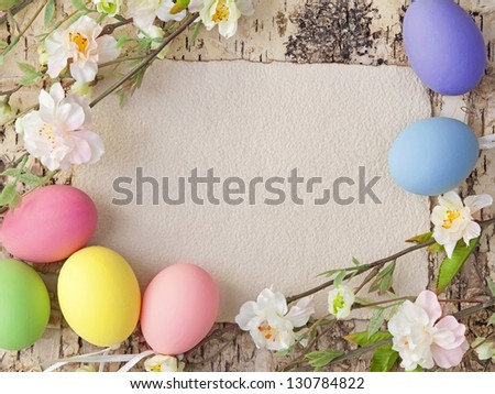 Easter eggs and blank note on wooden background - stock photo