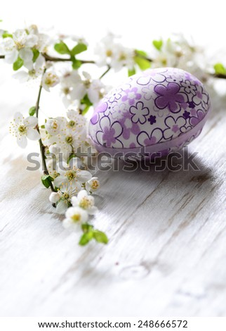 Easter eggs and branch with flowers on wooden background - stock photo