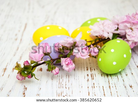 Easter eggs and cherries blossom on a old wooden background