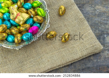 Easter eggs and Easter chocolate bunny on rustic wooden table - stock photo