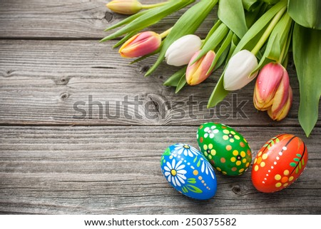 Easter eggs and fresh spring tulips on weathered wooden background - stock photo