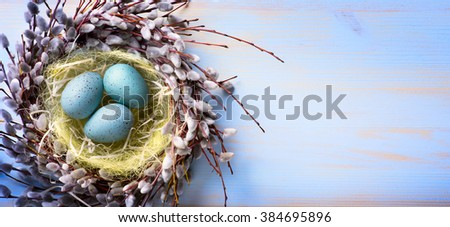 Easter eggs and spring flowers on blue wood background  - stock photo