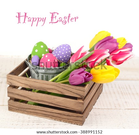 Easter eggs and spring tulips in a wooden box. An easter background with space for the text.