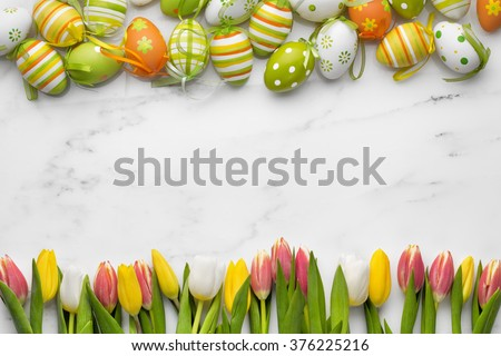 Easter eggs and tulips on white marble - stock photo