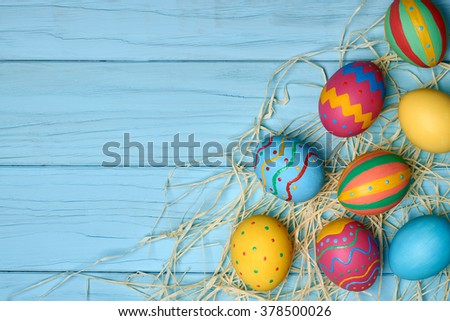 Easter eggs background. Hand painted multicolored decorated eggs on green straw, blue wood, copyspace. Unusual creative holiday greeting card  - stock photo