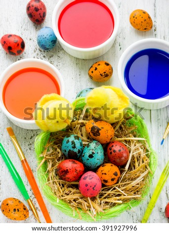 Easter eggs basket and paint on white background - stock photo