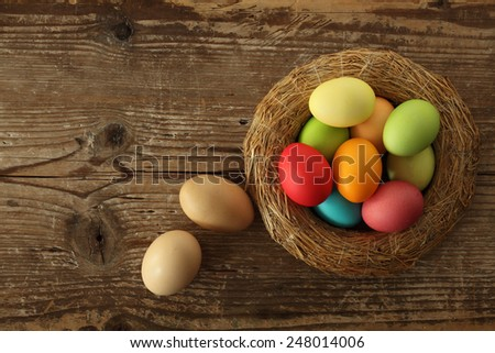 Easter eggs basket on wooden background - stock photo