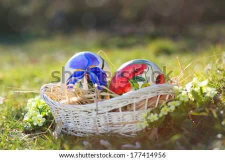 Easter eggs hand painted in a wicker basket . Natural spring light - stock photo