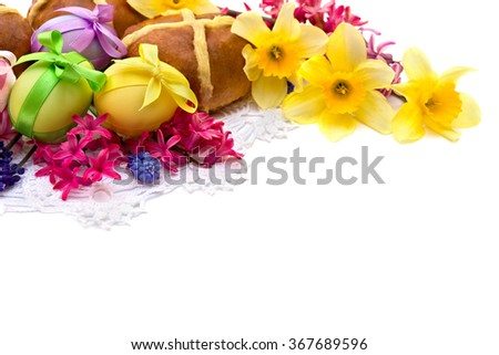 Easter eggs, hot cross bun, narcissus and hyacinth on white background with space for text. - stock photo