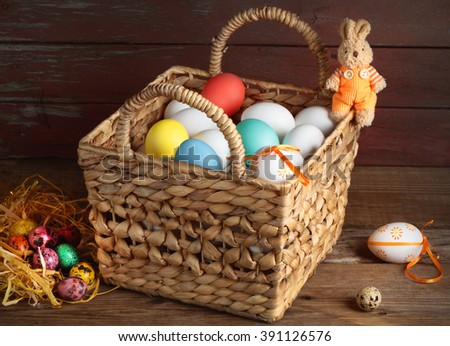 Easter eggs in a basket toy Bunny on the wood table - stock photo