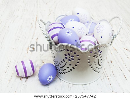 Easter eggs in a metal pot on a old wooden background - stock photo