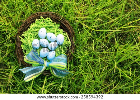 Easter eggs in a nest outside in the grass.  - stock photo