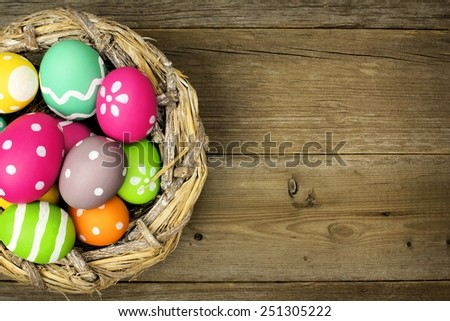 Easter eggs in a nest over an old wood background - stock photo