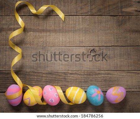Easter Eggs in a Row with Ribbon frame on a Rustic Wooden Background with room or space for copy, text. - stock photo