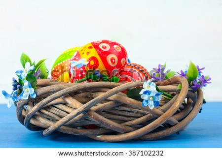 Easter eggs in beautiful and different colors are in the wreath  on blue wooden table isolated on white background