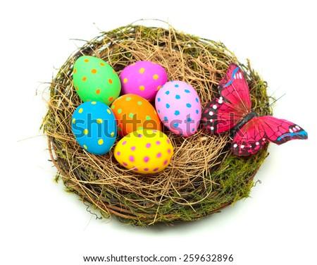 Easter eggs in bird's nest over white background - stock photo