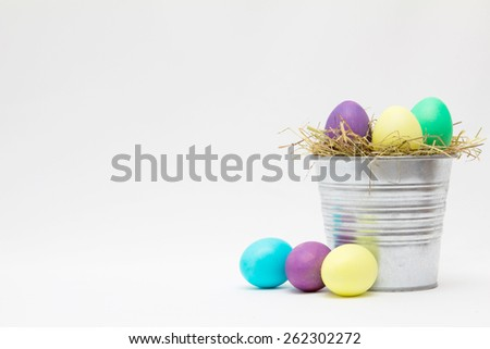 Easter eggs in bucket on light background - stock photo