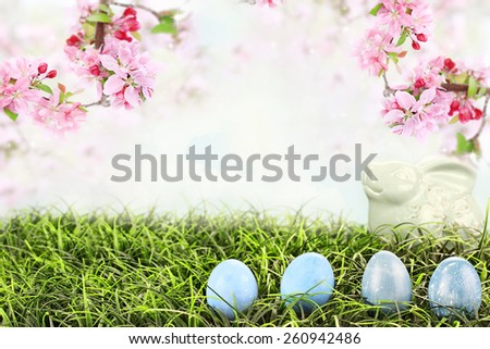 Easter eggs in grass with beautiful Crab Apple blossoms hanging overhead. Extreme shallow depth of field with selective focus on eggs.  Bunny in background is a generic object. - stock photo