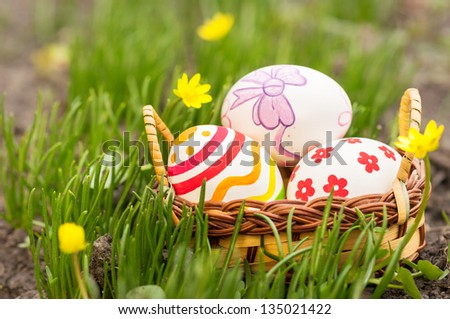 Easter Eggs in little basket on green grass