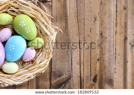 Easter eggs in nest on color wooden background - stock photo
