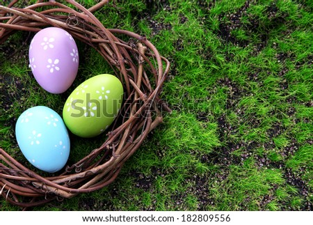 Easter eggs in nest on green grass background