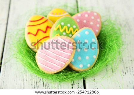 Easter eggs in nest on white wooden background - stock photo