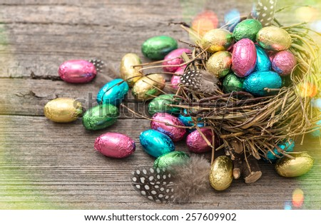 Easter eggs in nest on wooden background. Festive still life with multicolor chocolate sweets. Retro style toned picture with light leaks  - stock photo